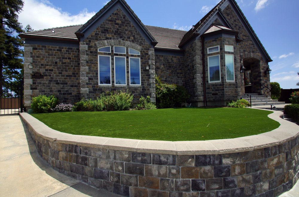 Artificial lawn with veneer stone retaining wall & stone caps in the front yard.