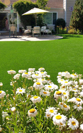 Artificial lawn installed in a backyard with a beautiful landscape