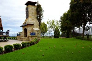 Artificial grass behind stone patio and fire place