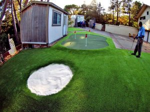 Putting green with three holes and a sand trap